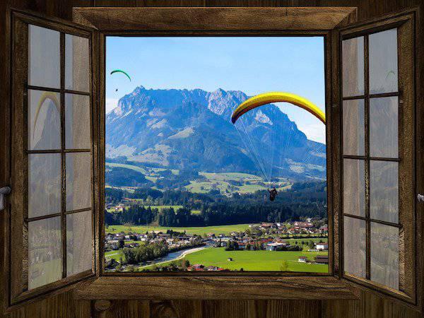 vol en parapente a travers la fenêtre de la chambre